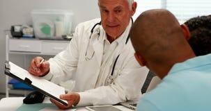 Männlicher Doktor, der ärztlichen Attest mit Patienten bespricht stock video