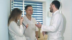 Männlicher Doktor, der die Tablette spricht mit zwei anderen Doktoren in der Krankenhaushalle hält Lizenzfreie Stockfotografie