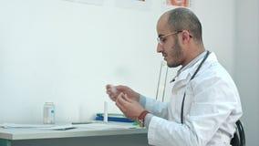 Männlicher Doktor, der die Temperatur auf Thermometer überprüft und medizinische Form ausfüllt stock video footage