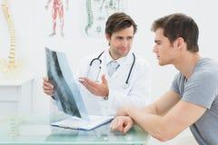 Männlicher Doktor, der Dornröntgenstrahl Patienten erklärt Lizenzfreie Stockbilder