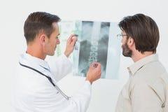 Männlicher Doktor, der Dornröntgenstrahl Patienten erklärt Lizenzfreies Stockbild