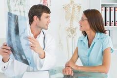 Männlicher Doktor, der Dornröntgenstrahl weiblichem Patienten erklärt Lizenzfreies Stockbild