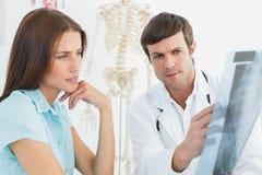 Männlicher Doktor, der Dornröntgenstrahl weiblichem Patienten erklärt Lizenzfreie Stockfotos