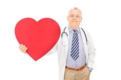 Männlicher Doktor, der ein großes rotes Herz hält Stockbilder