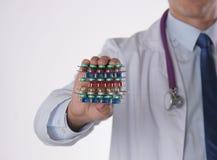 Männlicher Doktor, der einen Stapel vieler verschiedenen Pillen hält Lizenzfreie Stockfotografie