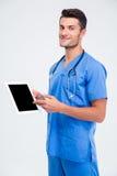 Männlicher Doktor, der Finger auf Tablet-Computer-Schirm zeigt Lizenzfreie Stockfotos
