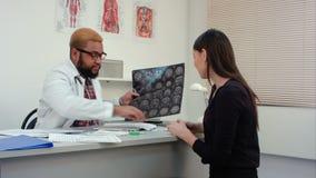 Männlicher Doktor, der Gehirnröntgenstrahl zeigt, resultiert zum jungen lächelnden Frauenpatienten stock video footage