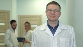 Männlicher Doktor, der Kamera während medizinisches Personal arbeitet an dem Hintergrund betrachtet stock video