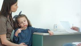 Männlicher Doktor, der Kardiogramm ernster Mutter mit kleinem Mädchen auf ihr Schöße erklärt stock video footage