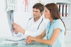 Männlicher Doktor, der Lungeröntgenstrahl weiblichem Patienten erklärt Stockfotos