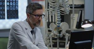 Männlicher Doktor, der menschliches Skelettmodell analysiert stock video