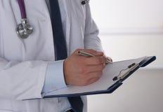Männlicher Doktor, der mit Ordner, auf weißem Hintergrund steht Lizenzfreie Stockfotos
