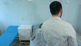 Männlicher Doktor, der mit Patientinnen auf dem Tropfenfänger stillsteht in der Krankenstation spricht stock video