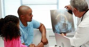 Männlicher Doktor, der Röntgenstrahlbericht mit Patienten bespricht stock video footage