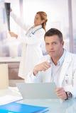 Männlicher Doktor, der am Schreibtisch tut Schreibarbeit sitzt Lizenzfreies Stockbild
