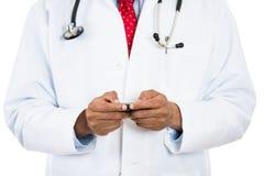 Männlicher Doktor, der an seinem Telefon simst Lizenzfreie Stockfotos