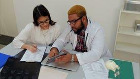 Männlicher Doktor, der seinem weiblichen Auszubildenden zeigt, wie man Formen unter Verwendung der Tablette ausfüllt stock video