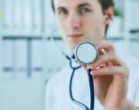 Männlicher Doktor, der Stethoskop für Überprüfung zeigt Doktor mit Stethoskop in der Hand auf Krankenhaushintergrund für medizini Lizenzfreie Stockfotos