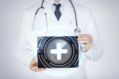Männlicher Doktor, der Tabletten-PC mit medizinischer APP hält stockfotografie