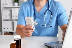 Männlicher Doktor, der am Tisch sitzt und Flasche hält Stockfotografie