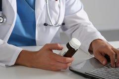 Männlicher Doktor, der am Tisch sitzt und Flasche mit Pillen hält Stockfoto