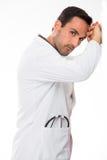 Männlicher Doktor, der zu einer Wand sich lehnt Stockfotografie