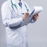 Männlicher Doktor füllt geduldige Karte stockfoto
