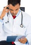 Männlicher Doktor im Laborkittel, der Lesungspatienten-Diagramm beim Sitzen auf einem Stuhl hält stockbild