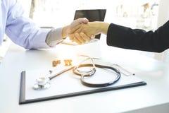 Männlicher Doktor im weißen Mantel, der Hand zum weiblichen Patienten nach s rüttelt stockbilder