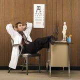 Männlicher Doktor mit Füßen auf Schreibtisch lizenzfreie stockbilder
