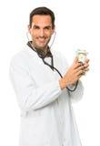 männlicher Doktor mit Stethoskop auf Geld Stockbild