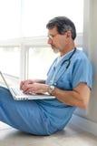 Männlicher Doktor oder Krankenschwester gesetzt mit Laptop-Computer stockfotos