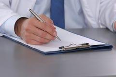 Männlicher Doktor schreiben auf den Schreibtisch mit Reagenzglas Stockfotografie