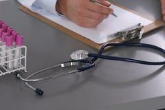 Männlicher Doktor schreiben auf den Schreibtisch mit Reagenzglas Lizenzfreies Stockbild