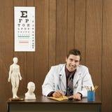 Männlicher Doktor am Schreibtischschreiben lizenzfreie stockfotos