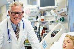 Männlicher Doktor With Sleeping Patient in der Unfallstation Lizenzfreie Stockfotografie