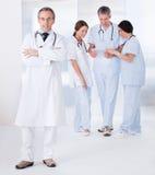 Männlicher Doktor vor Team Stockbild