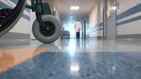 Männlicher Doktor Walking durch die lange Halle im Krankenhaus stock footage
