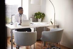 Männlicher Doktor Wearing White Coat im Büro, das an der Schreibtisch-Funktion auf Laptop sitzt stockfoto