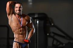 Männlicher Eignungs-Konkurrent, der seine gewinnende Medaille zeigt Stockbild
