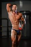 Männlicher Eignungs-Konkurrent, der seine gewinnende Medaille zeigt Stockfoto