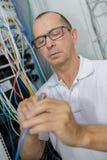 Männlicher Elektriker, der an fusebox arbeitet stockbilder
