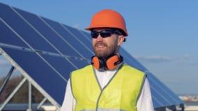Männlicher Experte zieht weg von einem Sonnenkollektor um und hebt seinen Sturzhelm an Konzept der alternativen Energie stock footage