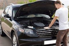 Männlicher Fahrer, der seinen Automotor überprüft lizenzfreies stockfoto