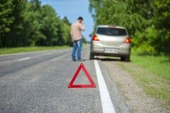 Männlicher Fahrer nach Zusammenbruch auf dem Straßenrand lizenzfreies stockbild
