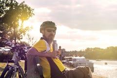 Männlicher Fahrradreiter, der auf der Bank sitzt Stockbilder