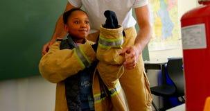 M?nnlicher Feuerwehrmann helfendes Afroamerikanerm?dchen, zum der Feueruniform im Klassenzimmer zu tragen Schulm?dchen smilin stock video