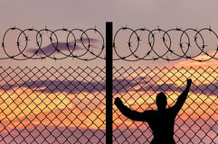 Männlicher Flüchtling des Schattenbildes und ein Stacheldrahtzaun Stockfotos