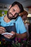 Männlicher Florist, der Bestellung am Handy entgegennimmt lizenzfreies stockbild