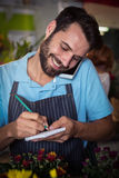 Männlicher Florist, der Bestellung am Handy entgegennimmt lizenzfreies stockfoto